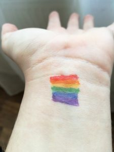 A photo of an outstretched hand with a small tattoo of a rainbow color filled rectangle, representing LGBT pride.