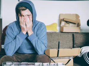 A white young adult man sitting on a couch, wearing a blue hoodie and covering his face with his hands, surrounded by moving boxes, feeling very overwhelmed and in need to anxiety treatment in Katy, TX.