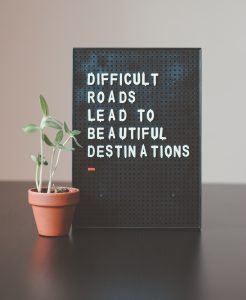 "A black letter board with white letters reading ""Difficult roads lead to beautiful destinations"" boded next to a small green plant inside a brown pot, offering hope for those who seek anxiety treatment in Katy, TX."