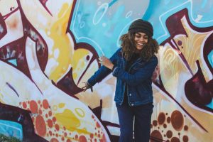 A black woman wearing a knitted black hat, a denim jacket and blue jeans, joyfully standing in front of a brightly painted wall feeling relieved of her anxiety after working with a Katy, TX counselor.