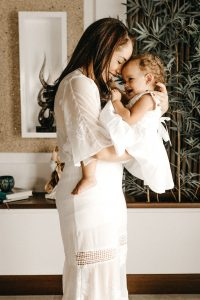 A photo of a mom and daughter wearing white dresses, mom holding daughter about 10 months old, facing her, and smiling into each others faces. Mom received postpartum anxiety treatment that helped her overcome postpartum anxiety disorder and postpartum panic attacks. Mom went to Anne Russey Counseling in Kathy, TX near West Houston.