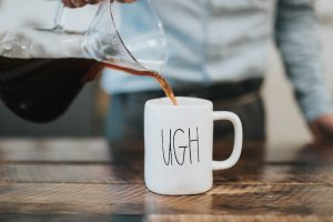 An image of someone pouring coffee into a coffee mug that says UGH representing the fact that sometimes in counseling in Katy, TX you may feel annoyed by or angry at your therapist. Anne Russey Counseling provides therapy and counseling in West Houston, Katy, TX 77494.