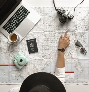 A photo taken looking over a woman planning a fantasy vacation as a method of self care. The image shows a map laid out on a table, with a laptop, a camera, a coffee mug, a passport and sunglasses. Planning an imaginary vacation is a self care strategy suggested by Katy, TX counselor Anne Russey. Anne Russey Counseling provides counseling services in Katy, TX near West Houston.