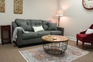 A photo of the inside of Anne Russey Counseling's office, showing a plush grey couch with decorative pillows, a coffee table, tall lamp in the corner and a decorative vintage rug in Katy, TX 77494.