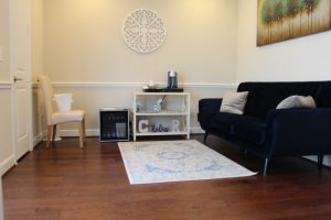 A photo of the comfortable waiting room containing a plush navy blue velvet sofa, a white chair, a fridge full of cold water bottles and a single cup coffee and tea maker, inside Anne Russey Counseling in Katy, TX.