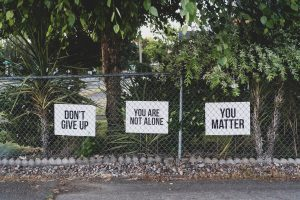 Black and white posters hung on a fence that say don't give up, you are not alone and you matter. Words of encouragement for parents experiencing postpartum anxiety in Katy, TX. Treatment for postpartum anxiety is available and can help.
