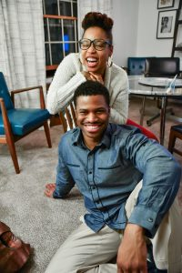 A photo of a young African American heterosexual couple posing happily on the floor, smiling and laughing enjoying quality time with one another during the holidays thanks to effective marriage counseling in southeast Houston.