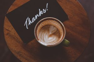 A color photo of a latte with hearts in the foam, and a black and white thank you note set out on a small round wooden table, from a husband to his wife, who have been engaged in relationship counseling in Friendswood, Texas.