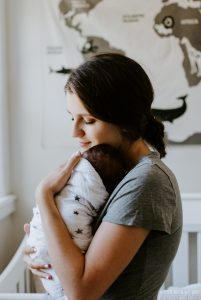 White mother holding swaddled newborn baby upright facing her, close to her chest looking down towards ground. Mom is feeling relieved after seeking counseling for postpartum depression in Katy, TX.