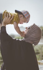 An outdoor photo of a mom wearing a hijab holding up her approximately 10 month old son up in the air, looking each other in the face, smiling and feeling less anxious and overwhelmed after seeking counseling for postpartum anxiety in Katy, TX.