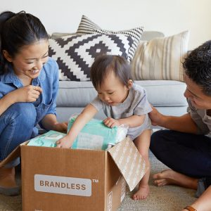 Photo of avian baby about 11 months old playing in box while mom and dad smile. Mom attended postpartum anxiety counseling with a Katy, TX therapist.