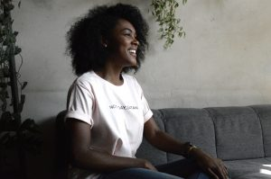 A photo of a black woman wearing a white t-shirt and bluejeans, sitting on a grey sofa, looking to the right of the screen. She's smiling, and feeling relief after seeking out anxiety treatment from Anne Russey Counseling in Katy, TX. Anne Russey is an anxiety therapist near Houston, TX. Anne Russey Counseling provides anxiety treatment and counseling for anxiety in her Katy, TX office and via Telehealth in Texas.