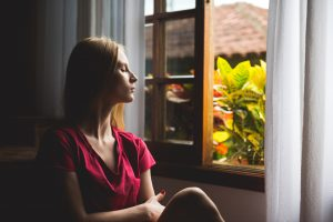 A woman looks out the window of her home in Katy, TX while she's maintaining social disctance during the coronavirus outbreak. She's practicing mindfulness and meditation strategies to cope with her anxiety about the health crisis.