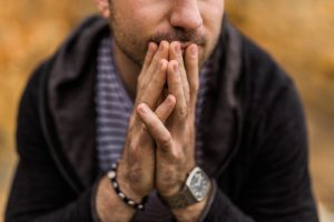 A cropped image of a white man holding his hands up to his face, folded as if he's praying. The man is experiencing a panic attack and looking for counseling for panic attacks and counseling for anxiety in Houston, TX. The man will begin anxiety treatment near Houston, TX at Anne Russey Counseling. Anne Russey Counseling is based in Katy, Texas and offers counseling for panic attacks and anxiety attacks.