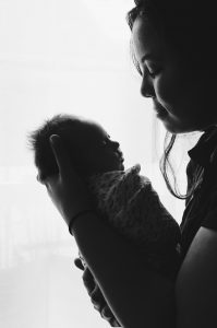 A profile greyscale photograph of a woman holding a swaddled newborn carefully facing her. The mother is trying to adjust to postpartum in the COVID-19 pandemic. She has contacted Anne Russey Counseling for telehealth for postpartum depression treatment in Texas.