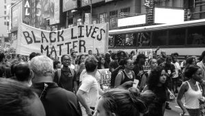 "Black and white image of protesters on a crowded city stressing holding a sign that reads ""BLACK LIVES MATTER."" Anne Russey Counseling is concerned about racial disparities and injustice in Houston, Texas."
