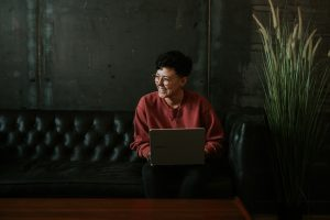 Androgynous person sitting on a sofa holding a laptop and smiling. This person has just finished an online counseling session with Anne Russey Counseling based in Katy, Texas.