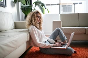 A black woman sitting on the floor propped up against a tan sofa, engaged in an online therapy session on her laptop in Plano, Texas.
